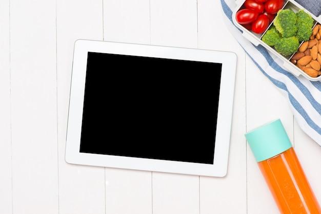 노트북, 유리에 오렌지 주스, 직장에서 플라스틱 기구가 있는 도시락에 신선한 샐러드