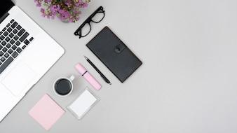 コーヒーカップと灰色の背景に文房具付きのノートパソコンのトップビュー