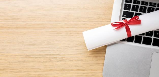 卒業証書とラップトップの上面図
