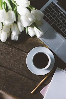 Вид сверху ноутбуков и тюльпанов на деревянном фоне