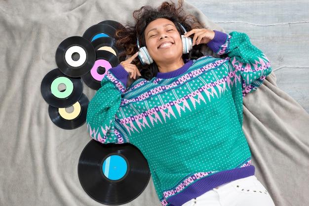 彼女の周りのビニールレコードで音楽を聴いて床に横たわっているラテンの女の子の上面図。