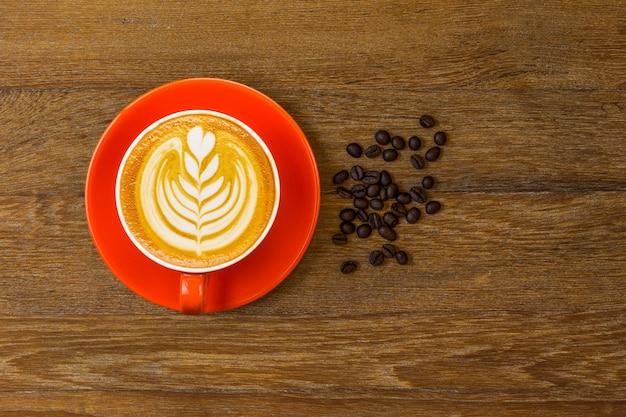 コーヒー豆で飾られたラテアートと赤いカップのラテコーヒーまたはカプチーノコーヒーの上面図