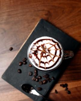 木製のテーブルのガラスのラテマキアートコーヒーのトップビュー