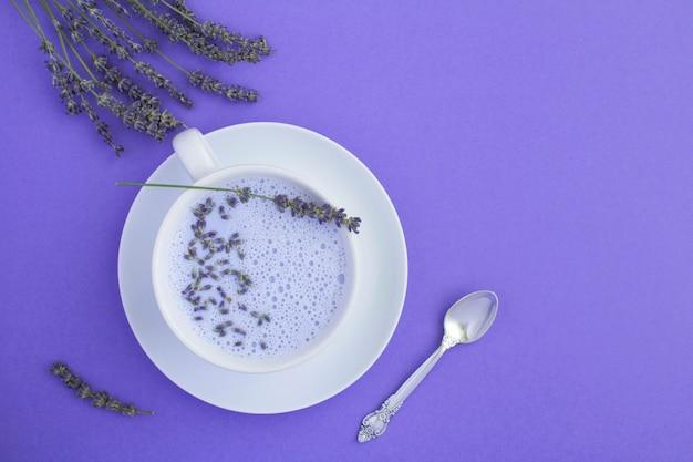 Вид сверху на лавандовое лунное молоко в белой чашке на фиолетовом