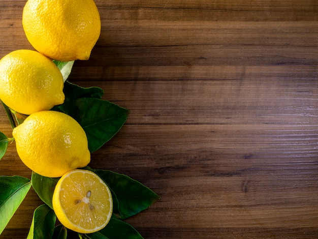 Вид сверху лимона и зеленых листьев на деревянных фоне