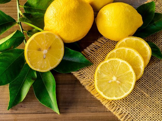 Вид сверху лимона и зеленых листьев на деревянных