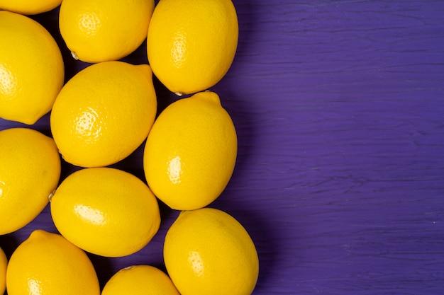 Взгляд сверху лимона на фиолетовой деревянной поверхности
