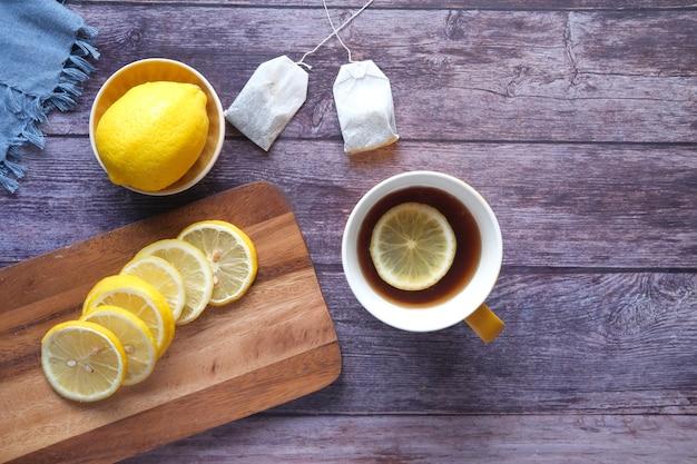 Вид сверху чай с лимоном и ломтик лимона на деревянных фоне