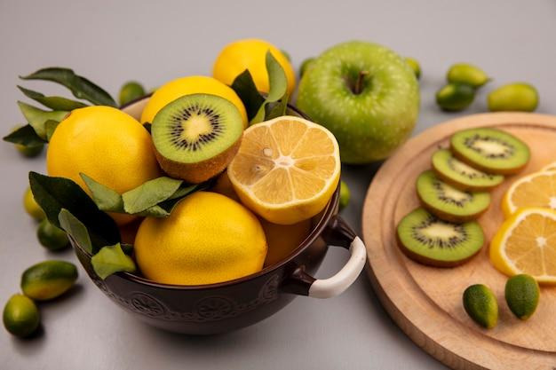 Вид сверху лимонов на миске с киви и ломтиками лимона на деревянной кухонной доске с кинканами и яблоком, изолированным на белой стене