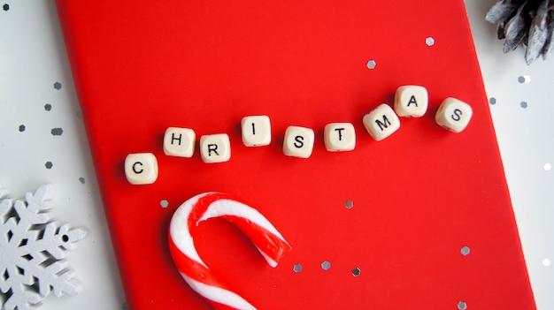 Вид сверху надписи «рождество» в красной записной книжке на белом фоне рядом с праздничными украшениями.