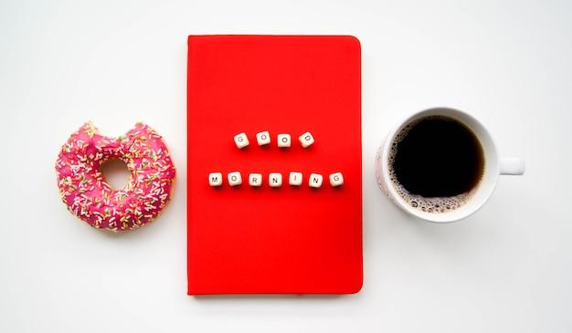 Вид сверху надписи «доброе утро». красный блокнот рядом с откушенным пончиком и черным кофе или чаем