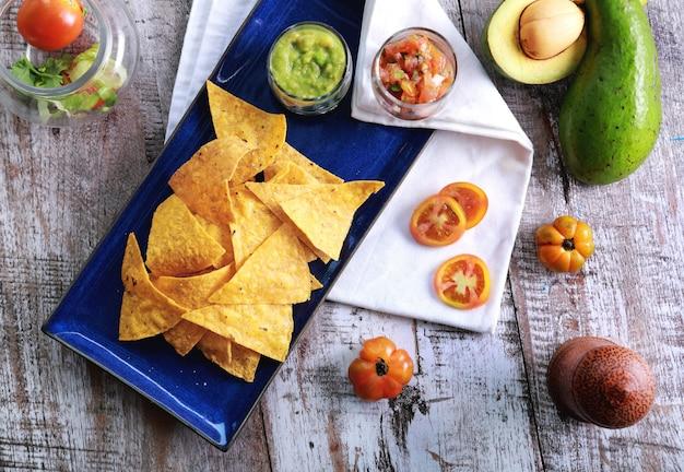 Вид сверху на легкие и хрустящие кукурузные чипсы с сальсой и гуакамоле на синей тарелке с деревянным столом на заднем плане