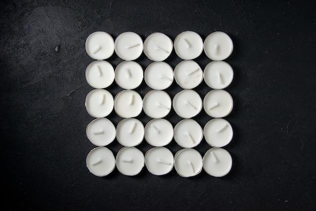 Вид сверху на светящиеся свечи квадратной формы на темной стене