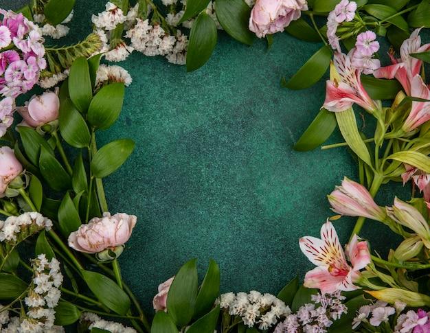Вид сверху светло-розовых цветов с ветвями листьев на зеленой поверхности