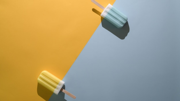 Вид сверху лайма и голубым малиновым ароматом фруктового мороженого и копирования пространство на плоской лежал желтый и синий фон