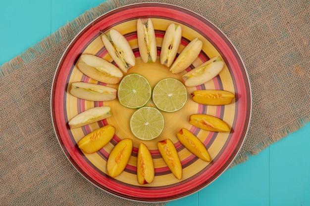 Вид сверху ломтиков лайма с яблоками и персиком на тарелке на бежевой салфетке на синей поверхности