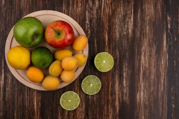 Вид сверху ломтиков лайма с персиковыми абрикосами и яблоком на деревянной поверхности