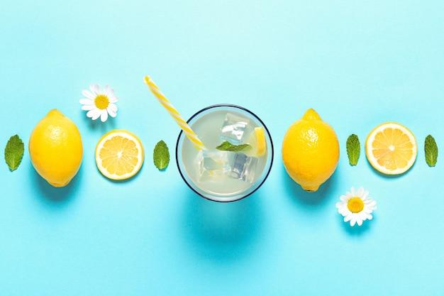 Вид сверху лимонада и ломтиков лимона на синем фоне с copyspace.