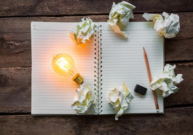 Вид сверху освещенной лампочки рядом с бумажными шариками