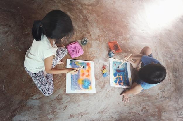 어린 아시아 아이들이 함께 물색을 칠하고 집에서 즐거운 시간을 보내는 최고의 전망.