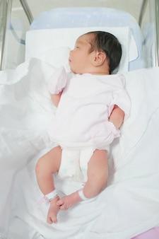 침대에 누워 있는 작은 아시아 신생아 소녀의 상위 뷰