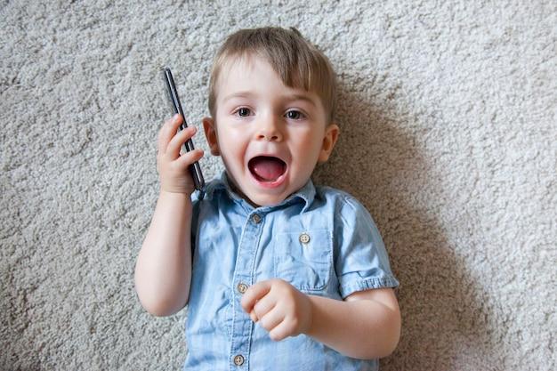 幸せな表情でスマートフォンを保持している小さな男の子の平面図です。