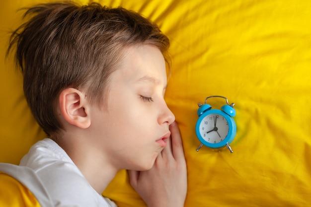 朝、目覚まし時計を頭の近くに置いて黄色いベッドで寝ている少年の上面図。