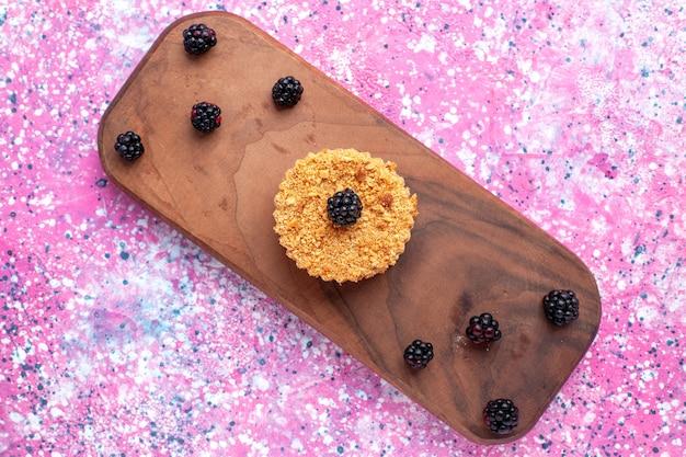 분홍색 표면에 딸기와 작은 케이크의 상위 뷰