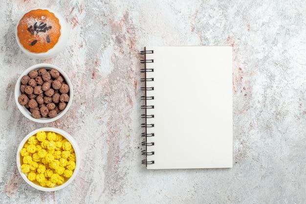 白のキャンディーとメモ帳と小さなケーキの上面図