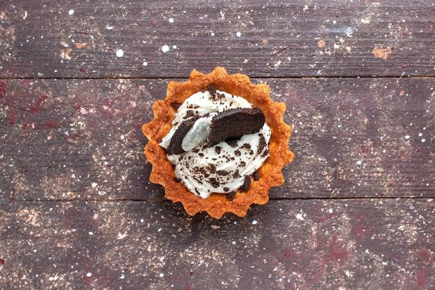 Вид сверху маленького торта со сливками и шоколадом, изолированного на деревянном коричневом, бисквитном сладком пироге