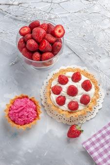 白い机の上のクリームと新鮮な赤いイチゴピンククリームケーキ、ケーキフルーツベリービスケットクリームと小さなケーキの上面図