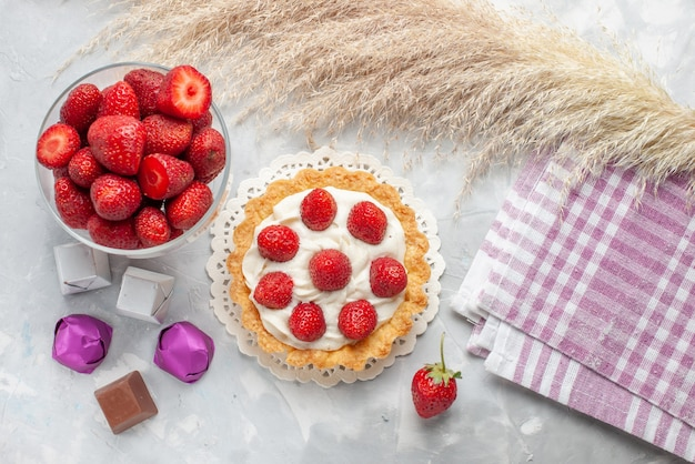 ホワイトライトデスク上のクリームと新鮮な赤いイチゴピンククリームケーキ、ケーキフルーツベリービスケットクリームと小さなケーキの上面図