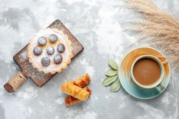 フルーティスと砂糖の粉とバングルと牛乳の光の上の小さなケーキの上面図、ケーキの甘いビスケットの甘い