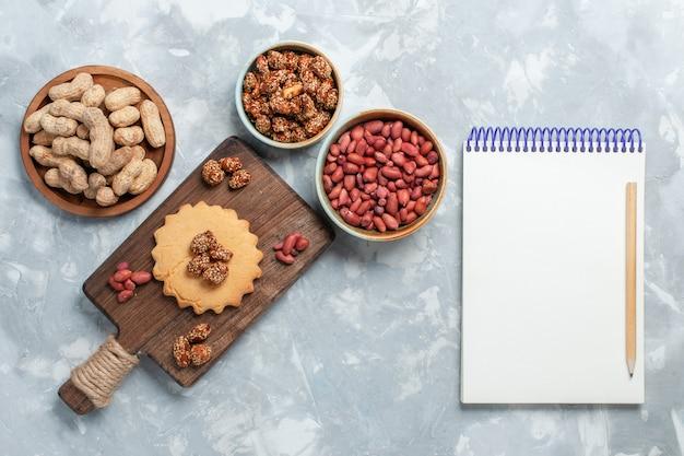 明るい白い表面にピスタチオとナッツの小さなケーキの上面図