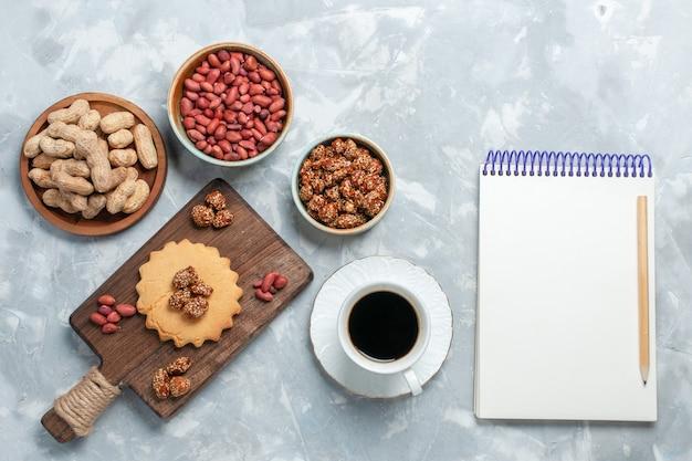 明るい白い表面にお茶とナッツのピスタチオカップと小さなケーキの上面図