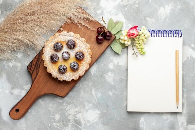 Вид сверху на маленький торт с сахарной пудрой, фруктовый крем и блокнот на свете, фруктовый сладкий чай с кремом для торта
