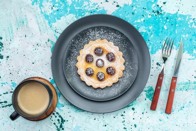 Вид сверху на маленький торт с сахарной пудрой, фруктовый крем внутри тарелки на свету, фруктовый сладкий чай