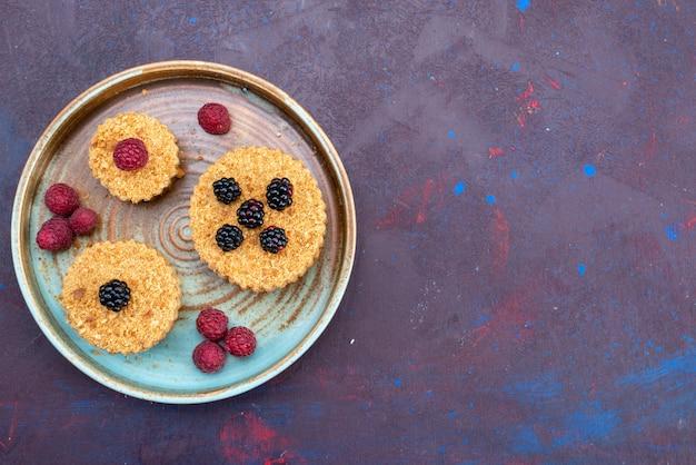Вид сверху сладких и вкусных пирожных с ягодами на темной поверхности