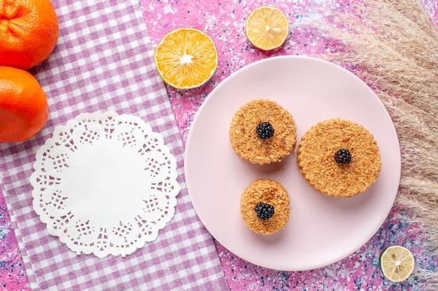 분홍색 표면에 접시 안에 딸기와 작은 케이크의 상위 뷰