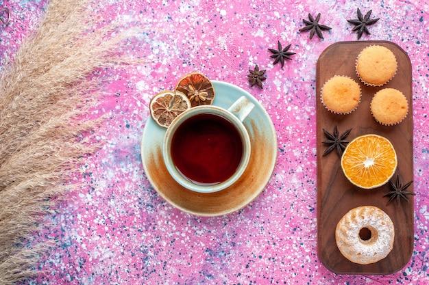 淡いピンクの表面にオレンジスライスとお茶のカップと小さなケーキの上面図