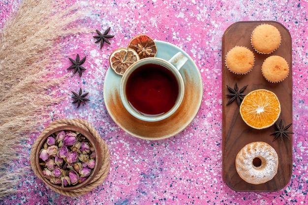 Вид сверху маленьких пирожных с долькой апельсина и чашкой чая на светло-розовой поверхности