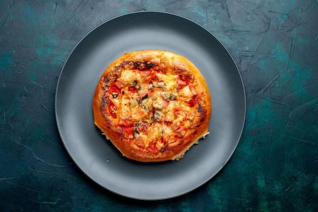 Вид сверху маленькой сырной пиццы круглой формы внутри тарелки на темно-синей поверхности