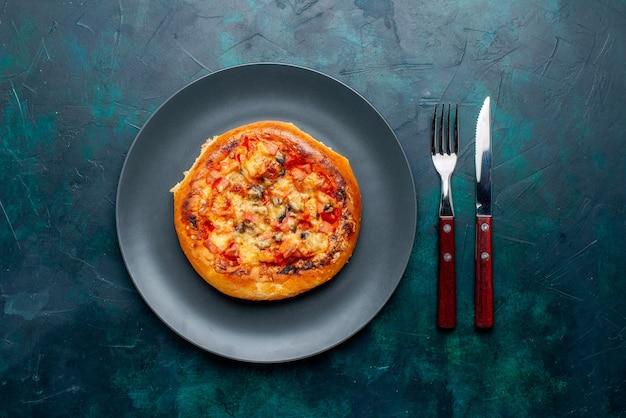 Вид сверху маленькой сырной пиццы круглой формы со столовыми приборами на темно-синей поверхности