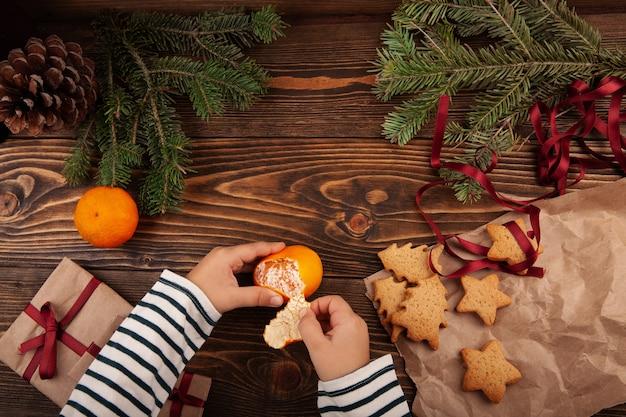 木製のテーブルでみかんやみかんの果実をはがしている小さな子供の上面図。