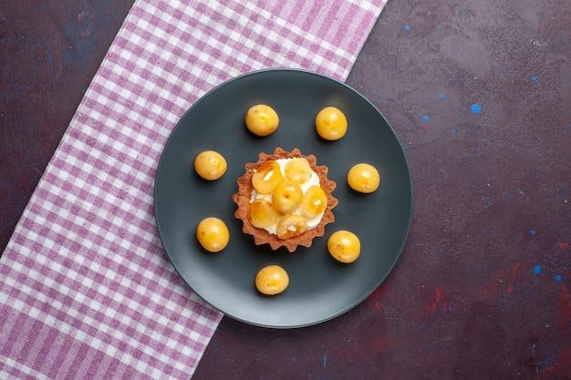Вид сверху на маленький сливочный торт со свежей черешней внутри тарелки на темном полу, фруктовый торт, бисквит, сладкий сахар