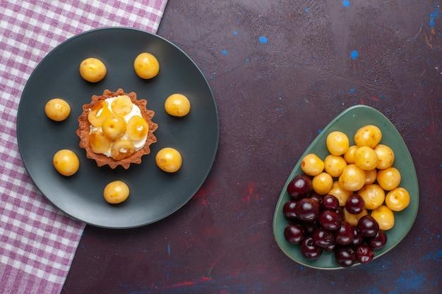 Вид сверху маленького сливочного торта со свежей черешней внутри тарелки на темной поверхности