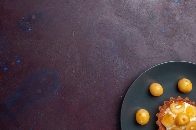 暗い表面のプレートの内側に新鮮な甘いサクランボと小さなクリーミーなケーキの上面図