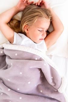 Вид сверху маленькой милой блондинки, спящей на белой кровати с поднятыми руками.