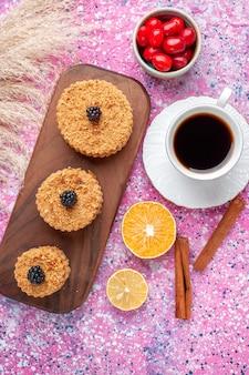 Вид сверху на маленькие вкусные пирожные с корицей и чаем на светло-розовой поверхности