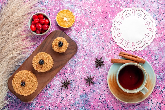 Вид сверху на маленькие вкусные пирожные с корицей и чаем на розовой поверхности